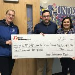 Check presented by Trevor Brittsan (center) of First Interstate Bank to Shelley Moore (left), Principal of Sam Case, and Kristin Becker (right), Principal of Yaquina View Elementary. Standing in front of a Sam Case classroom in need of a Lockdown Shade.